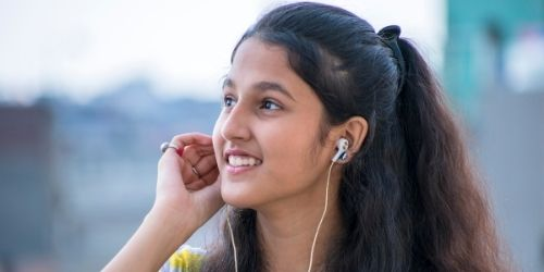A girl listening to music with earbuds